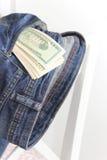 在牛仔裤的一个口袋的金钱在椅子后面的  免版税图库摄影