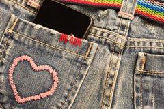 在牛仔裤的口袋的巧妙的电话 免版税库存照片