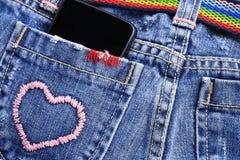 在牛仔裤的口袋的巧妙的电话 库存照片