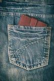 在牛仔裤的后面口袋的皮革棕色钱包 库存图片