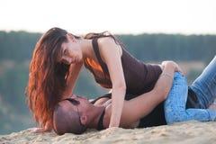 在牛仔裤的夫妇在海滩 免版税库存照片