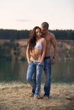 在牛仔裤的夫妇在海滩 库存照片