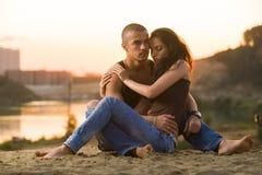 在牛仔裤的夫妇在海滩 图库摄影