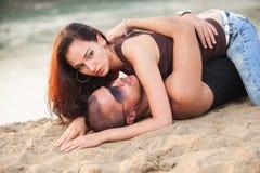 在牛仔裤的夫妇在海滩 库存图片