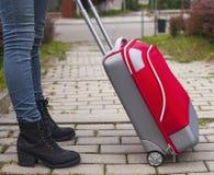 在牛仔裤的女孩脚的带着在一个红色旅行手提箱附近 免版税库存照片
