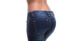 在牛仔裤的女性屁股。 免版税库存照片