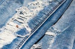 在牛仔裤的孔 棉花牛仔布详细资料织品牛仔裤纹理 库存照片