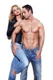 在牛仔裤的性感的夫妇在白色墙壁 图库摄影