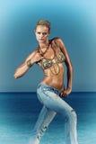 在牛仔裤的时装模特儿由海 库存照片