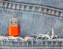 在牛仔裤的红色USB缆绳装在口袋里的特写镜头 免版税库存图片