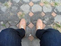 在牛仔裤的年轻时尚人` s在地板上的腿和起动 免版税库存图片