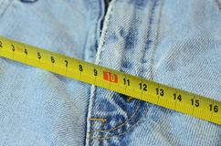 在牛仔裤背景的措施磁带 库存照片