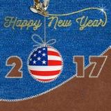 在牛仔裤背景的新年快乐2017美国国旗 缝合的织品补花 免版税库存图片