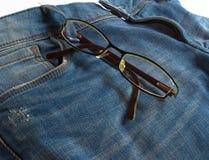在牛仔裤背景的现代玻璃 库存图片