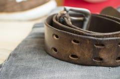 在牛仔裤背景的粗砺的皮带 图库摄影