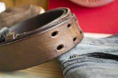 在牛仔裤背景的粗砺的皮带 库存图片