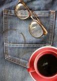 在牛仔裤背景的红色咖啡杯与镜片(放松概念) 图库摄影