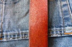 在牛仔裤背景的被扣紧的皮带 库存图片