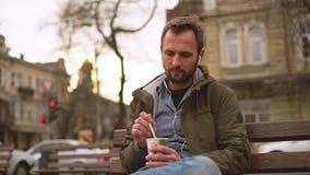 在牛仔裤衬衣图画的英俊的男服在咖啡用棍子坐在耳机的长凳听的音乐 影视素材