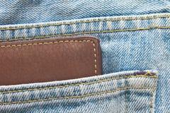 在牛仔裤长裤的布朗钱包支持口袋 免版税库存照片