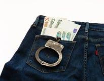 在牛仔裤零用钱和手铐是欧洲钞票和卢布 图库摄影
