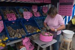在牡蛎街道商店前面的妇女在康卡尔,法国 免版税库存图片