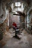 在牢房的红色理发椅 免版税库存照片