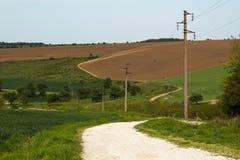 在牧场地和庄稼领域之间的绞的农村方式,横渡由传输耸立 库存照片