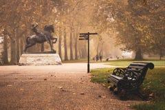 在物理能量雕象旁边的偏僻的长凳在海德公园 悲伤,忧郁,幽暗,寂寞 免版税库存图片