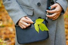 在特写镜头的小黑皮革提包 灰色co的女孩 库存照片