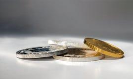 在特写镜头的金和银币在灰色背景 库存照片