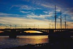 在特奥多尔・豪斯莱茵河桥梁的日落有一艘船的阴影的在美因法Kastel 免版税库存图片