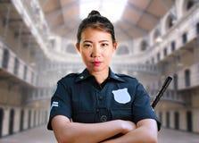 在状态监狱监狱大厅佩带的警察制服的年轻严肃和有吸引力的亚裔美国人卫兵妇女身分在罪行 免版税库存照片