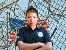 在状态监狱监狱barbwire篱芭佩带的警察的年轻严肃和有吸引力的亚裔美国人卫兵妇女身分 库存照片