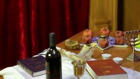 在犹太教堂的桌上是犹太新年的标志:款待,羊角号,摩西五经,酒,蜡烛 股票录像