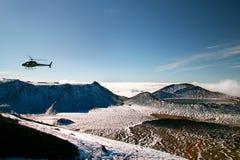在狂放的山多雪的风景的流浪的抢救直升机与在云彩,抢救的不定期船,新西兰上的深蓝色湖 免版税库存照片