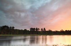 在狂放的森林湖的多雨日出 免版税库存照片