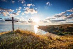 在狂放的海滩和美妙的日出的基督徒十字架 库存照片