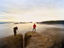 在狂放的自然的专业摄影师和远足者射击与一台数字照相机和三脚架 库存照片
