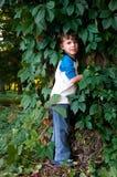 在狂放的葡萄中叶子的男孩  免版税库存照片