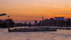 在狂欢河的老船在电视塔和Oberbaum的b柏林 免版税库存图片