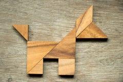 在狗形状的七巧板难题在木背景 免版税库存照片