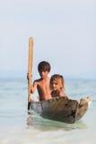 在独木舟的未认出的孩子在Mabul海岛 图库摄影