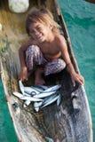 在独木舟的未认出的孩子有在Mabul海岛的鱼的 免版税库存照片