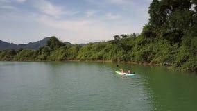 在独木舟风帆的上部后侧方夫妇向林业河岸 影视素材