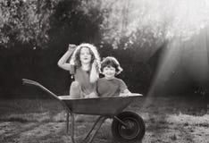 在独轮车的儿童乘驾 库存照片