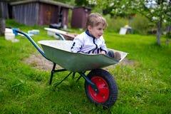 在独轮车里面的逗人喜爱的年轻男婴在庭院里 库存图片