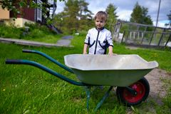 在独轮车附近的逗人喜爱的年轻男婴在庭院里 免版税图库摄影