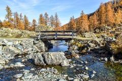 在狭窄的小河的老木桥在山 免版税库存图片