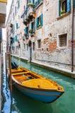 在狭窄的水运河的小船在威尼斯意大利 库存图片